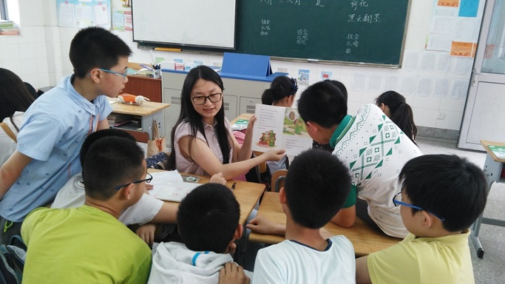 Dr. Zhu's student reads to young English learners.